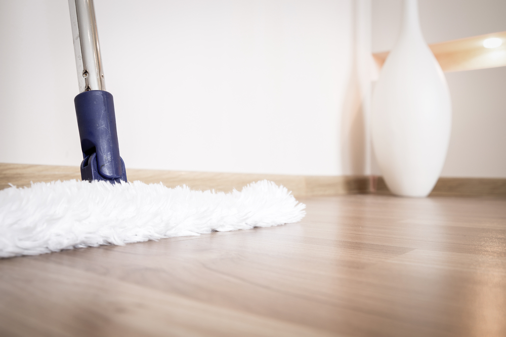 Service of cleaning hardwood floor from dust with white mop in house